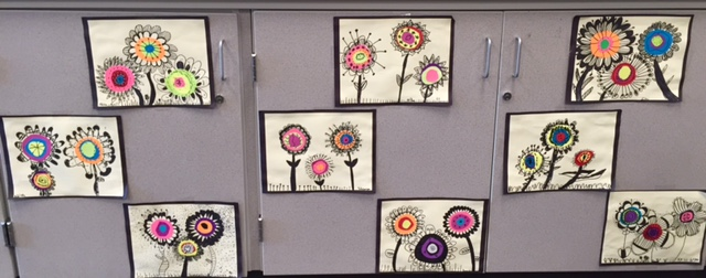 photo of student artwork in the style of Kadinsky: colorful round cut circles  and black pen to make flowers